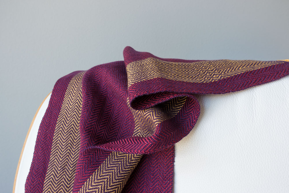purple and gold scarf draped on the back of a chair