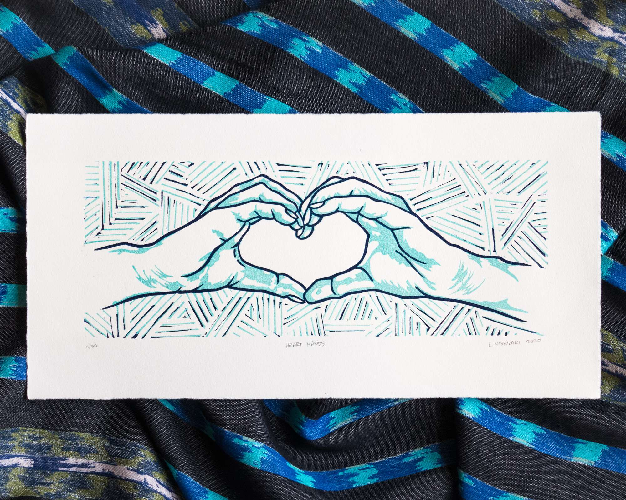 A horizontal print with dark navy and light turquoise ink on off-white paper with torn edges. Two hands form a heart shape; the simple outline is depicted in navy, and shadows are depicted in turquoise. The background is made up of lots of sections of parallel lines, in both navy and turquoise.