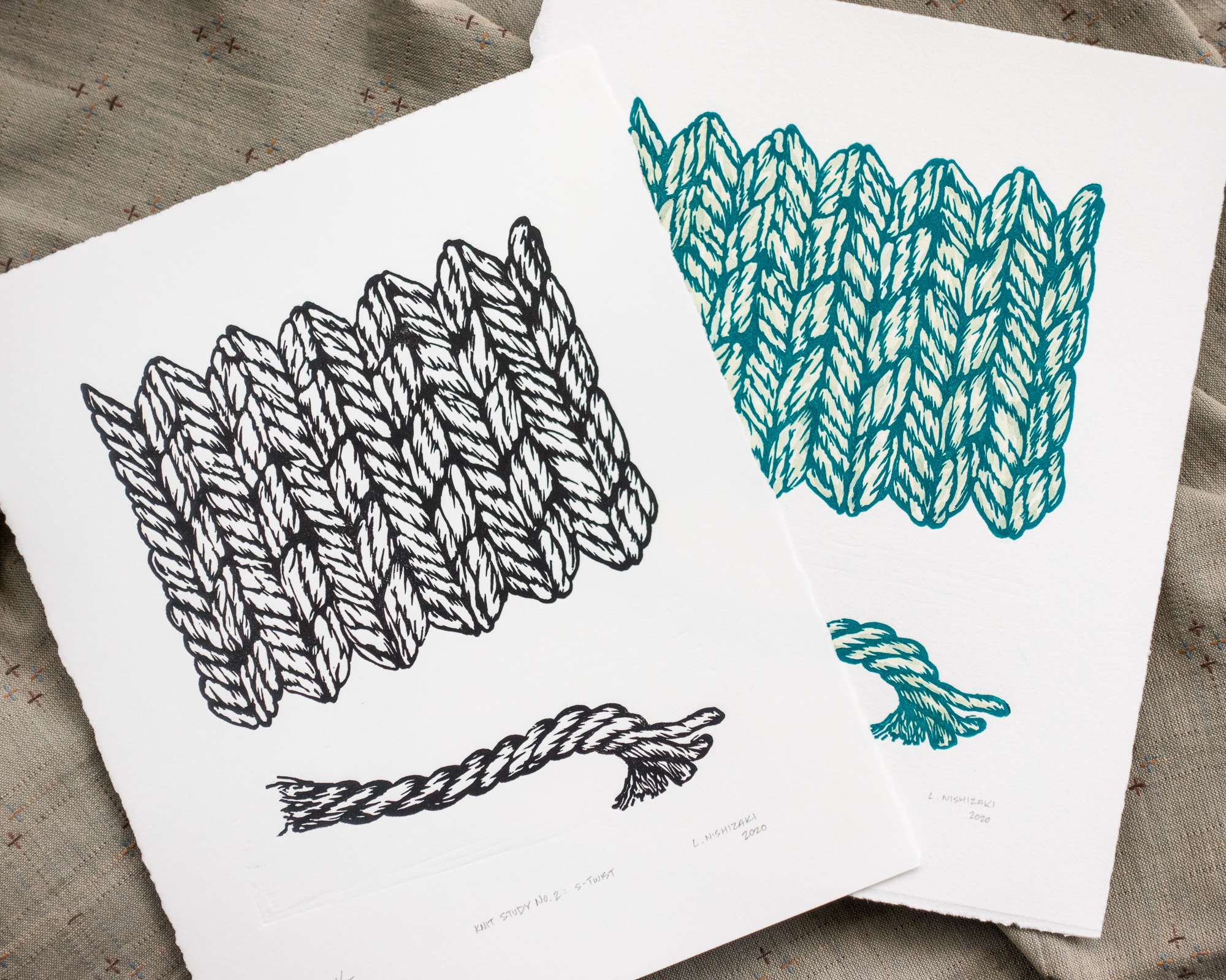 Two overlapping vertical prints on white paper, lying on top of a grey backdrop. Each print has a rectangular design of stockinette knitting stitches on top, and a depiction of a horizontal strand of yarn below. The left print is black; the right print is green with subtle green/yellow coloring.