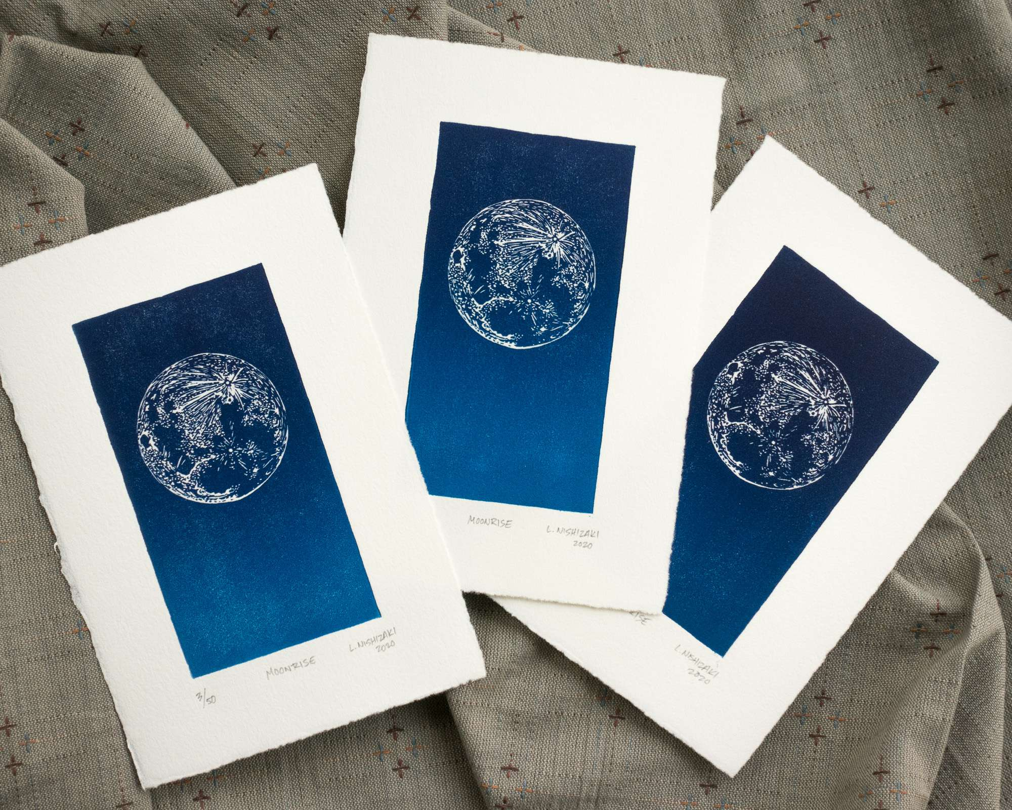 Three overlapping vertical prints, each depicting a moon in the top section of a blue rectangle. Each blue rectangle is dark blue at the top and fades to a lighter vibrant blue at the bottom. The color gradients of the three prints vary slightly in ink coverage and darkness.