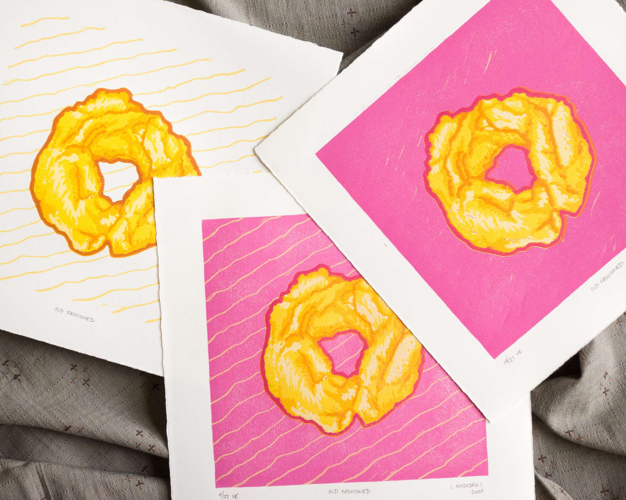 A trio of three square prints, slightly overlapping, of an old fashioned donut. The left-most print has yellow stripes in the background of a yellow and orange donut. The middle print has the same pattern but with a bright pink background. The right-most print has the same pattern with a bright pink background, minus the yellow stripes.