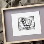 The print lying on grey matboard within a pale wood frame.